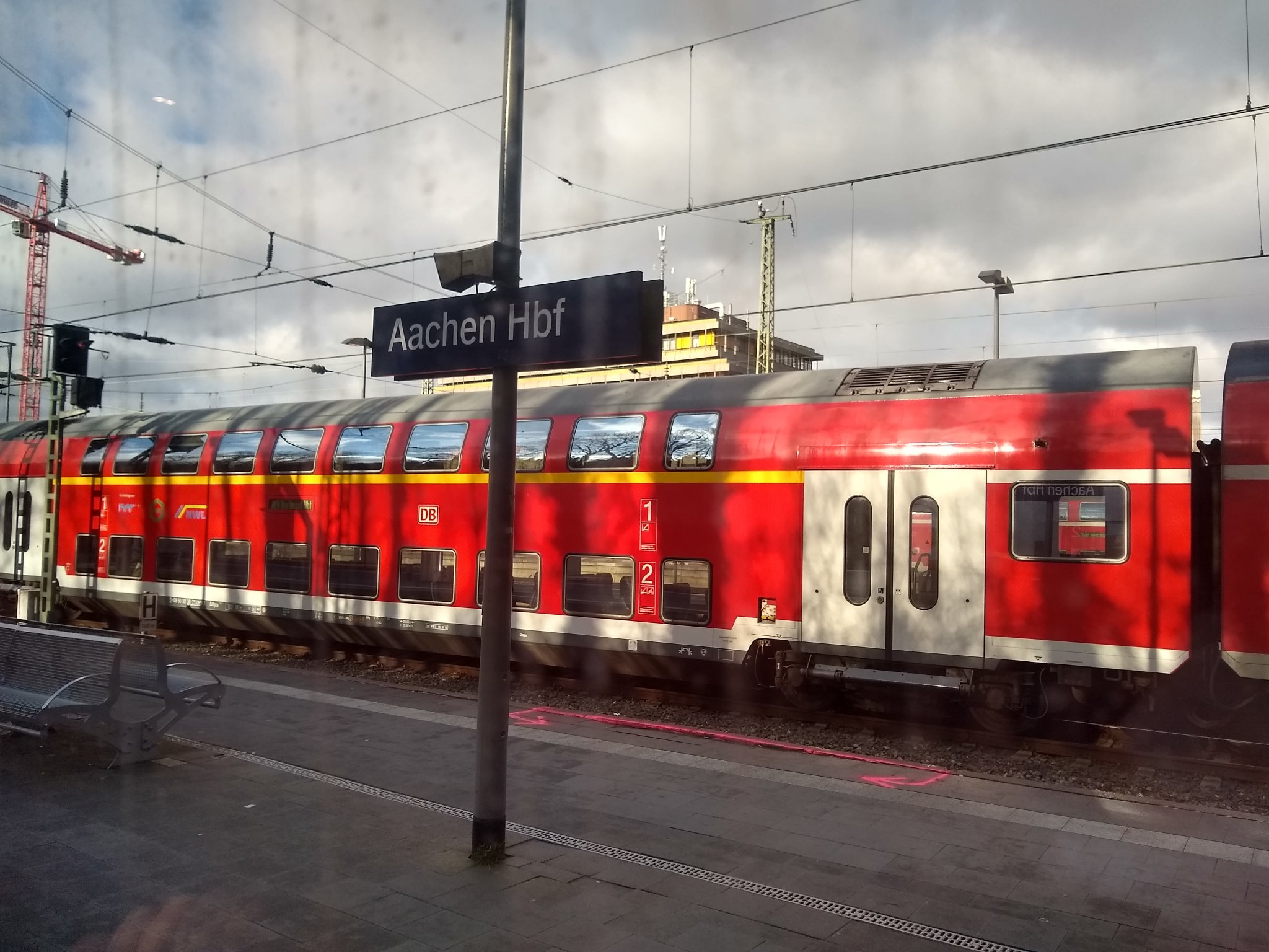 Platform sign saying Aachen Hbf with a double-decker red DB regional train