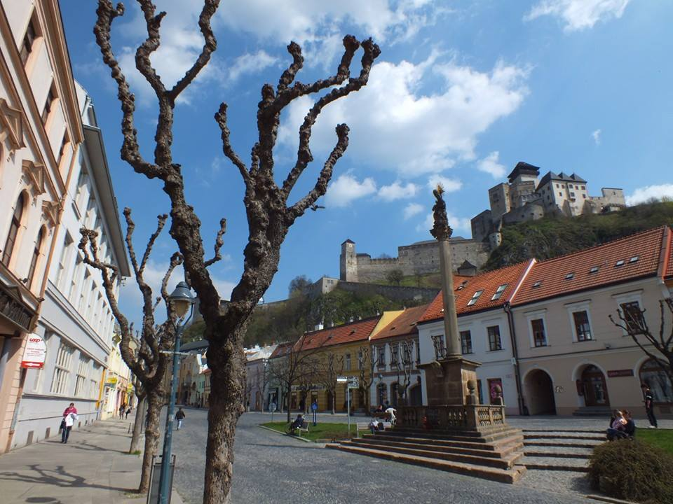 A street in Trenčín; the castle can be seen above the building's roof.